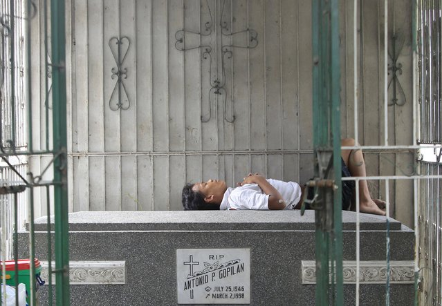 A man sleeps on top of a grave inside a public cemetery in Makati financial district of Manila October 31, 2015. (Photo by Janis Alano/Reuters)