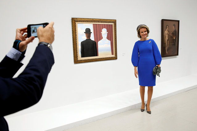 """Queen Mathilde of Belgium poses next to the painting """"La decalcomanie, 1966"""" (Decalcomania) as she visits the exhibition """"La trahison des images"""" (The Treachery of Images) on Belgian surrealist painter Rene Magritte (1898-1967) at the Centre Pompidou modern art museum, also known as Beaubourg, in Paris, France, October 5, 2016. (Photo by Benoit Tessier/Reuters)"""