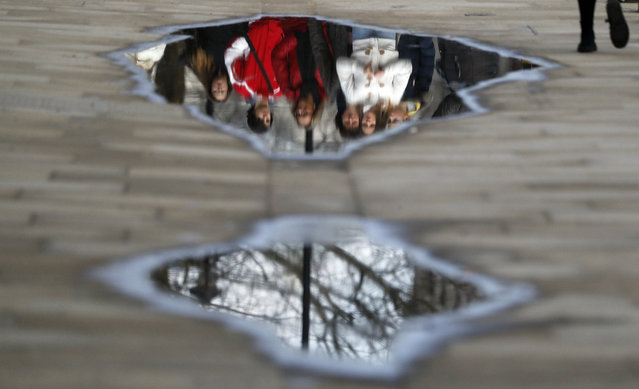 Pedastrians are reflected in a puddle in Westminster, London, Tuesday, March 13, 2018. (Photo by Frank Augstein/AP Photo)