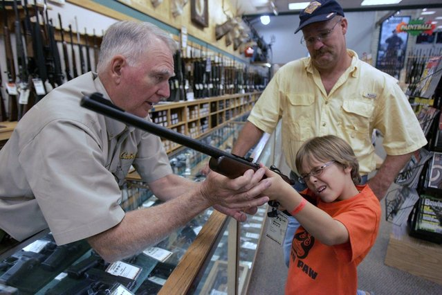 Hunter McConathy (C), 7, holds a hunting rifle with a short stock as his father Bryan (R) and Cabela's salesman Russ Duncan (L) watch him at the Cabela's store in Fort Worth, Texas June 26, 2008. Individual Americans have a right to own guns, the Supreme Court ruled on Thursday for the first time in history, striking down a strict gun control law in the U.S. capital. (Photo by Jessica Rinaldi/Reuters)
