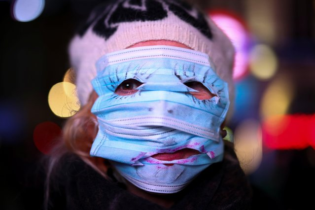 A woman uses protection masks to cover her face as protestors from the Million Mask March and anti lockdown protesters demonstrate, amid the coronavirus (COVID-19) outbreak in London, Britain on November 5, 2020. (Photo by Henry Nicholls/Reuters)
