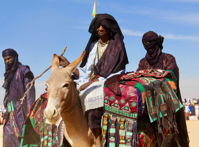 In this photo taken Saturday February 17, 2018, Tuareg men ride on camels during a festival in Iferouane, Niger. (Photo by Ludivine Laniepce/AP Photo)