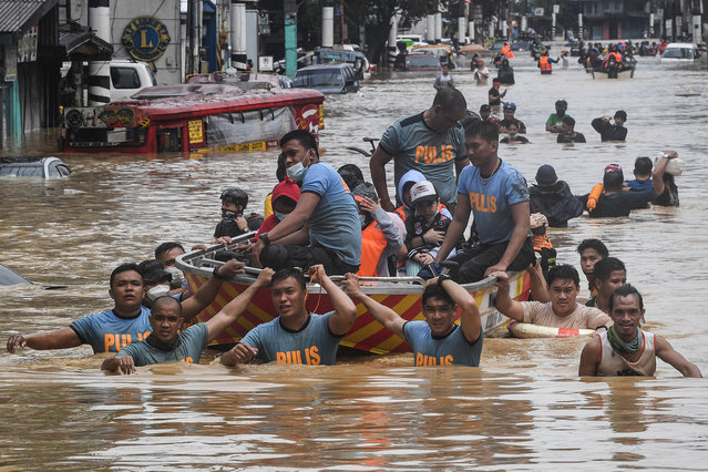 Rescuers pull a rubber boat carrying residents through a flooded street after Typhoon Vamco hit in Marikina City, suburban Manila on November 12, 2020. (Photo by Ted Aljibe/AFP Photo)