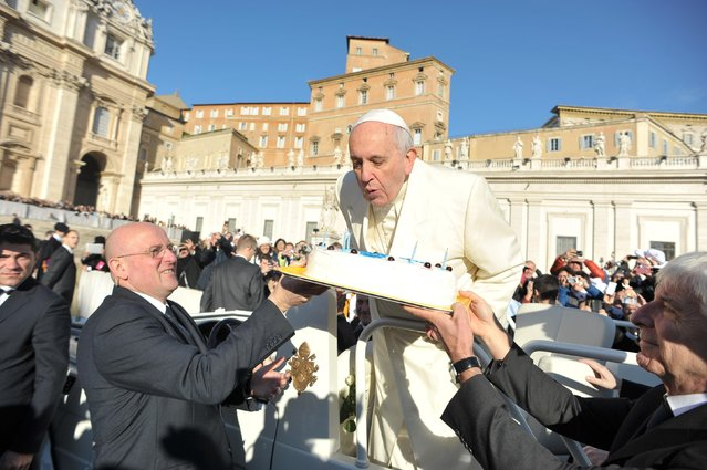 Pope Francis, who celebrates his 78th birthday, blows out candles on a cake as he arrives to lead his general audience at the Vatican, December 17, 2014. (Photo by Osservatore Romano/Reuters)