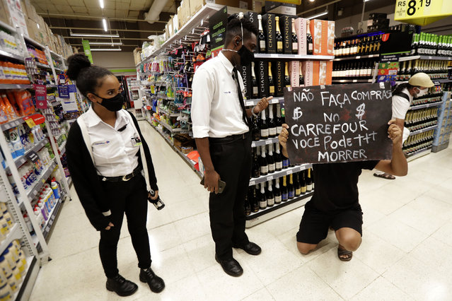 Carrefour supermarket security guards ask a demonstrator against the murder of Black man João Alberto Silveira Freitas, on Brazil's National Black Consciousness Day in Brasilia, Brazil, Friday, November 20, 2020. (Photo by Eraldo Peres/AP Photo)