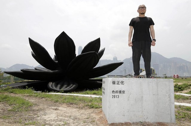 "Korean contemporary artist Choi Jeong Hwa poses with his inflatable sculpture, named 'Emptiness is Form.Form in Emptiness' during the ""Inflation!"" exhibition curated by Mobile M + on April 24, 2013 in Hong Kong. The inflatable artwork is one of six on display as part of the exhibition which is open from April 25, 2013 until June 9, 2013. (Photo by Jessica Hromas)"