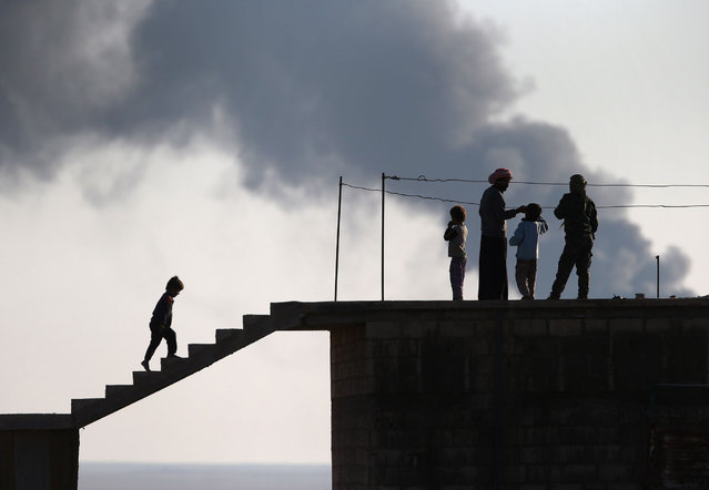 Local residents speak with a Kurdish soldier while an oil well burns in the distance on November 10, 2015 near the ISIL-held town of Hole in the autonomous region of Rojava, Syria. Troops from the Syrian Democratic Forces, a coalition of Kurdish and Arab units, are attacking ISIL extremists in the area near the Iraqi border. The predominantly Kurdish region of Rojava in northern Syria has become a bulwark against the Islamic State. (Photo by John Moore/Getty Images)