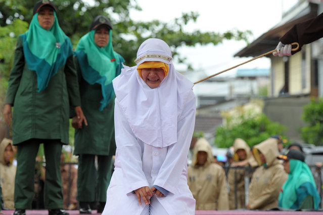 A Muslim girl gets caned 23 strokes after being caught in close proximity with her boyfriend in Banda Aceh on October 17, 2016. (Photo by Chaideer Mahyuddin/AFP Photo)