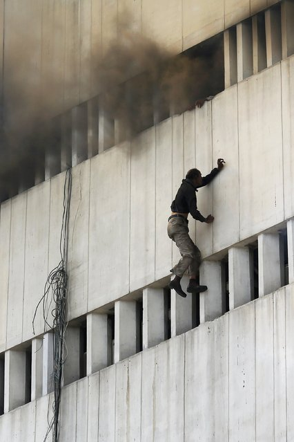 A man falls from a high floor of a burning building in central Lahore May 9, 2013. Fire erupted on the seventh floor of the LDA plaza in Lahore and quickly spread to higher floors leaving many people trapped inside the building. At least three people fell from the high floors trying to avoid the fire that engulfed the building, local media reports. (Photo by Damir Sagolj/Reuters)