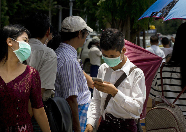 People wear masks to protect themselves against the swine flu on a main street, Tuesday, July 25, 2017, in Yangon, Myanmar. (Photo by Aung Shine Oo/AP Photo)