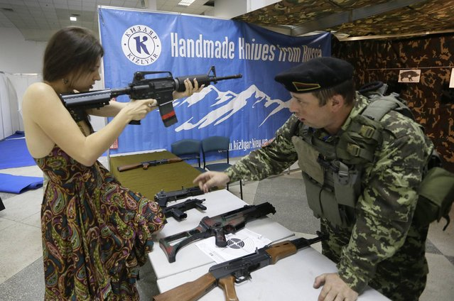 A Ukrainian woman handles a gun as a man explains how to handle it during an international weapons show in Kiev, Ukraine, Friday, May 17, 2013. The Ukrainian Ministry of Internal Affairs launched an initiative to change the law to allow Ukrainian citizens who have reached 18-years old to buy traumatic weapons, with the bill being submitted to Cabinet ministers for approval. (Photo by Efrem Lukatsky/AP Photo)
