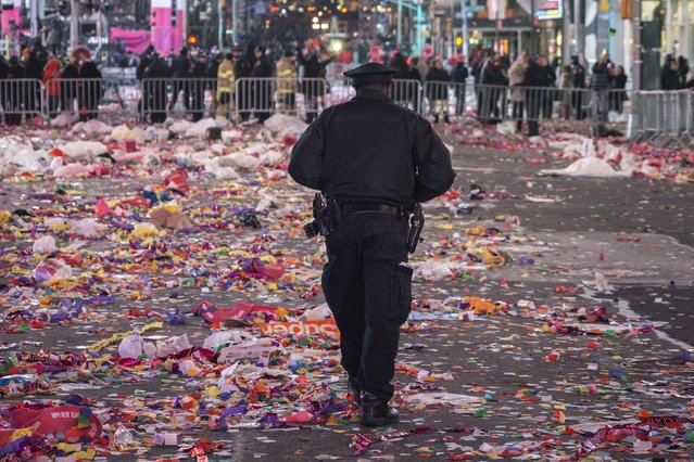 A New York Police Department (NYPD) officer walks through confetti covering a street after midnight during New Year's Eve celebrations in Times Square, New York January 1, 2015. (Photo by Zoran Milich/Reuters)