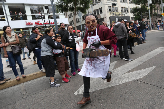 A man dressed as zombie runs as he participates in a Zombie Walk procession in Mexico City, Mexico, October 22, 2016. (Photo by Edgard Garrido/Reuters)