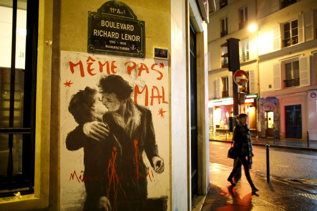 """A drawing which reproduces French photographer Robert Doisneau's picture """"Le baiser de l'Hotel de ville"""" (Kiss by the Town Hall) with the words """"Not even hurt"""" over it, is seen on a wall near the Bataclan concert hall, one of the sites of last Friday's deadly attacks in Paris, France, November 20, 2015. (Photo by Charles Platiau/Reuters)"""
