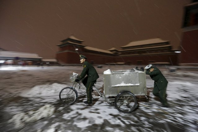 Paramilitary police officers transport snow from their camp outside the Wumen Gate of Forbidden City during snowfall, at night in central Beijing, China, November 22, 2015. (Photo by Jason Lee/Reuters)