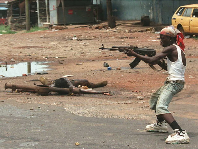 A boy, Kalashnikov in hand, leads a group of Charles Taylor's soldiers during heavy fighting around Monrovia's main military barracks, 16 April 1996 in Liberia. At least 15 corpses were scattered around. (Photo by Christophe Simon/AFP Photo)
