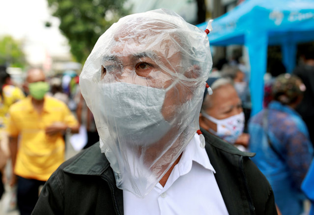 A man affected by the government's measures against the spread of the coronavirus disease (COVID-19) wears a protective face covering as he lines up for filing forms to request three months of monthly financial aid from the government in front of the Finance Ministry in Bangkok, Thailand, May 1, 2020. (Photo by Soe Zeya Tun/Reuters)