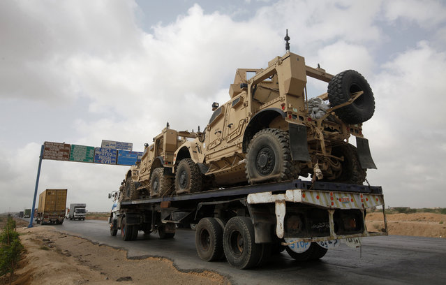 A trailer transports armored vehicles, used by NATO forces during the Afghan war, along a road after their arrival at Port Mohammad Bin Qasim, some 40 km (25 miles) from Karachi, on May 25, 2013. After more than ten year NATO and U.S. have started withdrawal of their equipments from Afghanistan, local media reported. (Photo by Athar Hussain/Reuters)