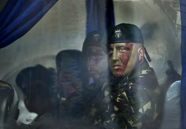 Romanian special forces servicemen wait on a bus before the beginning of the national day celebrations in Bucharest, Romania, Tuesday, December 1, 2015. Thousands gathered to watch a military parade. (Photo by Vadim Ghirda/AP Photo)