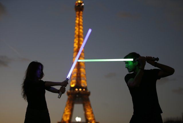 "Marion (L) and Nikola (R), members of the Sport Saber League, pose with their light sabers in front of the Eiffel tower in Paris, France, November 26, 2015. Three ""Star Wars"" fans opened the French Academy of the Sport Saber League in September 2015 due to the increase interest for light saber fighting and the upcoming  movie ""The Force Awakens"" which will premier in Paris, December 16th, two days before its worldwide official release. (Photo by Charles Platiau/Reuters)"