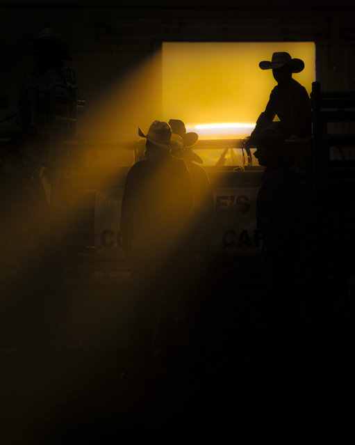 """Cowboy in a ribbon of light"". Rodeos always provide a sense of place. There's action, dirt, pride, you name it. It's a loud, flashy sport, with cheering and showboating. But on the underbelly are quiet moments. The moments between bucking broncs, beer drinking and the announcers crude jokes. Moments like this one, where a young boy waits patiently for the next horse to come charging out of the chutes. Location: Helena, Montana. (Photo and caption by Dylan Brown/National Geographic Traveler Photo Contest)"