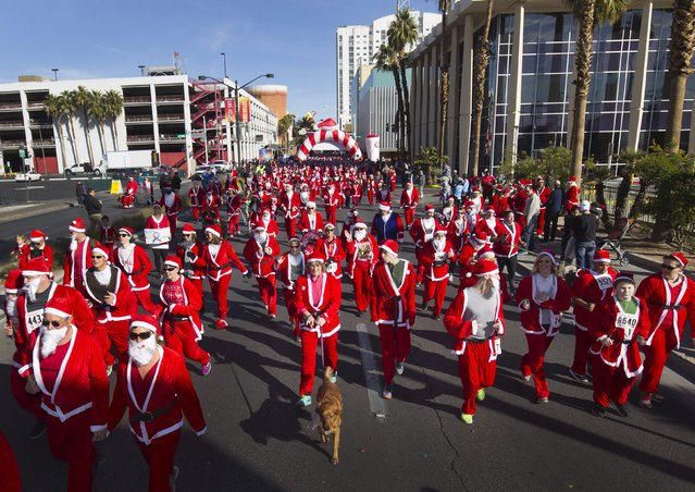 Runners dressed as Santa Claus head down Las Vegas Boulevard during the 11th annual Las Vegas Great Santa Run in downtown Las Vegas, Nevada, December 5, 2015. (Photo by Steve Marcus/Reuters)