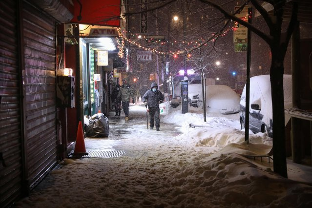 Pedestrians walk in the East Village during a snow storm, during the coronavirus disease (COVID-19) pandemic in the Manhattan borough of New York City, New York, U.S., February 1, 2021. (Photo by Caitlin Ochs/Reuters)