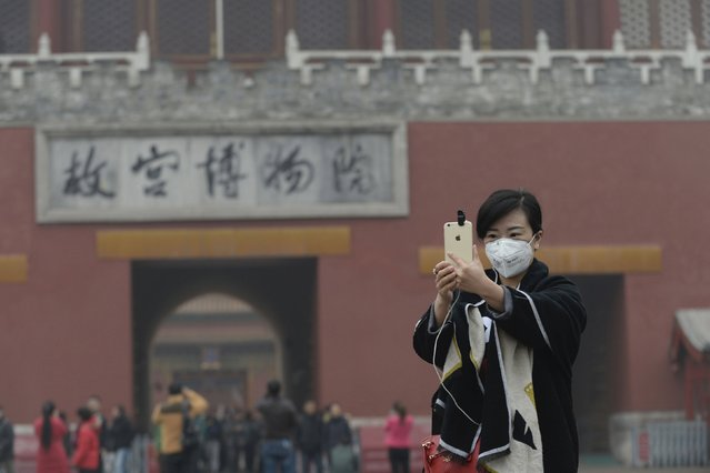 "A woman takes a selfie with her mobile phone in front of an entrance to the Forbidden City amid heavy smog after the city issued its first ever ""red alert"" for air pollution, in central Beijing, China, December 8, 2015. (Photo by Reuters/China Daily)"