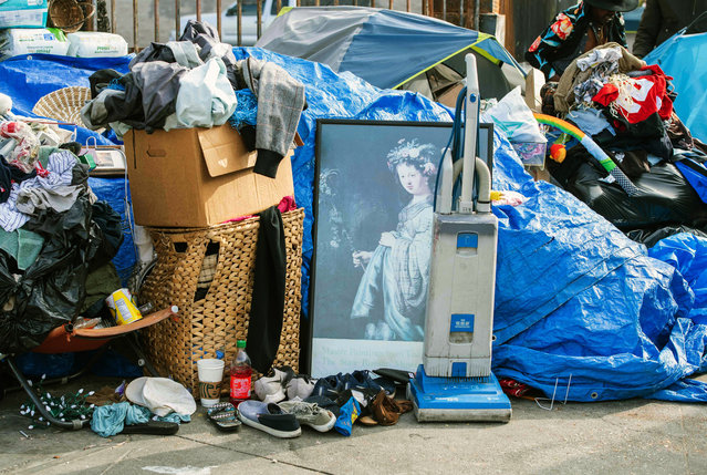 Items belonging to homeless people are seen on the sidewalk as L.A. Sanitation service sweep the street on February 8, 2021 in Hollywood, California. (Photo by Valerie Macon/AFP Photo)
