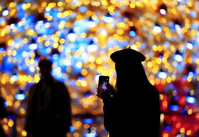 A Taiwanese woman takes a photo of a Christmas tree decoration at a street in Taipei, Taiwan,13 December 2015. (Photo by Ritchie B. Tongo/EPA)