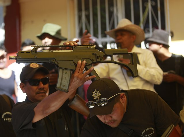 A Heckler-Koch HK G36C assault rifle, which was seized from a house during an operation, is held up by a member of the Community Police of the FUSDEG (United Front for the Security and Development of the State of Guerrero) during a presentation in the village of Petaquillas, on the outskirts of Chilpancingo, in the Mexican state of Guerrero, February 1, 2015. (Photo by Jorge Dan Lopez/Reuters)