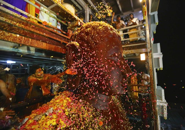 Devotees shower flowers on the 42-ft-tall monolithic statue of Lord Bahubali, also known as Gommateshwara, during the Mahamastkabhishekha or the head-anointing ceremony of the Jain god in the southern Indian town of Karkala, January 31, 2015. The ceremony is held every twelve years and draws thousands of followers of the Jain faith from around the world. (Photo by Abhishek N. Chinnappa/Reuters)