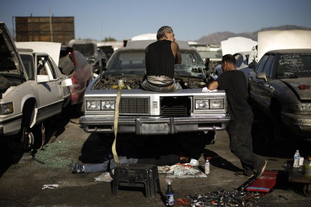 In this Wednesday, November 11, 2015 photo, three men gather around a junk car to salvage some parts at Aadlen Brothers Auto Wrecking, also known as U Pick Parts, in the Sun Valley section of Los Angeles. (Photo by Jae C. Hong/AP Photo)