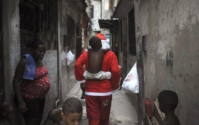 Leandro Wendell dos Santos, 14, wearing a Santa Claus costume, plays with kids as he walks along the alley of the Mare slums complex to distribute presents to children in Rio de Janeiro, Brazil, December 23, 2015. Leandro is part of a volunteer group of residents of Mare slums complex that distributes donated toys to children of the community. (Photo by Fabio Teixeira/Reuters)
