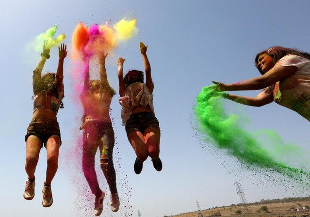 Indian girls apply colored powder on each other as they wear protective masks as a precautionary measure against coronavirus, during Holi festival celebrations in Bhopal, India, 26 March 2021. Holi marks the beginning of the spring season. Holi will be celebrated as the Hindu spring festival of colors across the country on 29 March. (Photo by Sanjeev Gupta/EPA/EFE)