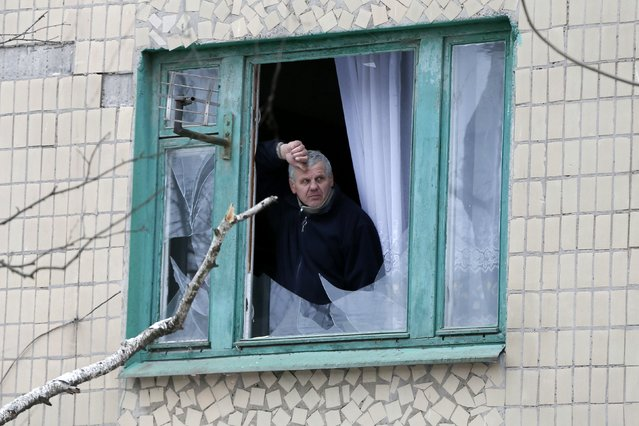 A man looks out of a window of a residential block damaged by a recent shelling in the town of Kramatorsk, eastern Ukraine February 10, 2015. (Photo by Gleb Garanich/Reuters)