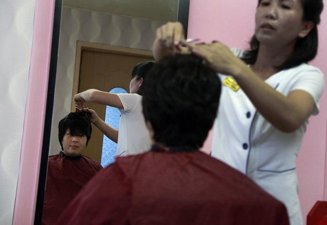 A woman has her hair cut at a hair salon at Munsu Water Park during in Pyongyang, North Korea, Tuesday, July 24, 2018. (Photo by Dita Alangkara/AP Photo)