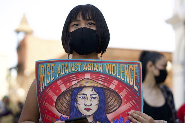 Ally Vega holds a poster by artist Pauline Cuevas, as she joins a rally against Asian hate crimes in El Pueblo de Los Angeles, Los Angeles Plaza Park, Saturday, March 27, 2021. Asian Americans and their allies held rallies Saturday in California, home of the nation's largest Asian population, to denounce shootings at massage businesses in Georgia and racism, xenophobia and misogyny. The gathered crowd demanded justice for the victims of the Atlanta spa shooting and for an end to racism, xenophobia and misogyny. (Photo by Damian Dovarganes/AP Photo)