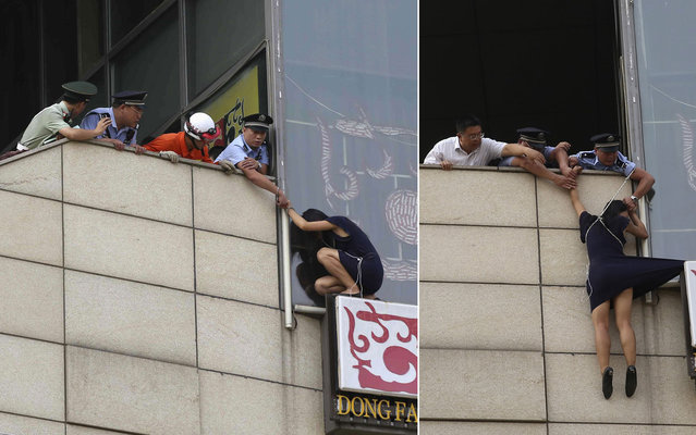 A police officer saves the life of a suicidal woman by handcuffing himself to her and throwing away the key. The desperate woman had climbed to the top of a bill board on a concrete wall in Beijing, China, on August 14, 2013. But her plight quickly attracted the attention of bystanders and police arrived to try and talk her down. When one of the officers was talking to her, he decided the only way to make sure she did not jump was by handcuffing himself to the woman. As the woman hung from the ledge the officer put the metal cuff across his wrist and the connected it to the woman. And in a determined bid to make sure she realised he was serious about saving her, he then threw the key over the ledge so they could not be separated. Police then used a length of rope to pull the woman back onto the building as she dangled above a sheer drop to the concrete pavement held by just her wrist. (Photo by Reuters/China Daily)