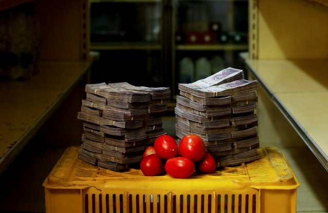 A kilogram of tomatoes is pictured next to 5,000,000 bolivars, its price and the equivalent of 0.76 USD, at a mini-market in Caracas, Venezuela August 16, 2018. It was the going price at an informal market in the low-income neighborhood of Catia. (Photo by Carlos Garcia Rawlins/Reuters)
