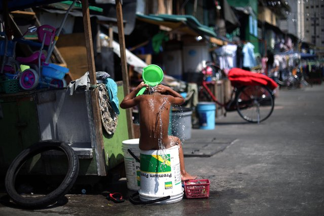 A Filipino boy takes a bath outside his house in Manila, Philippines on Tuesday, February 10, 2015. (Photo by Aaron Favila/AP Photo)