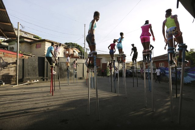 Members of the Keylemanjahro School of Art and Culture listen to instructions from one of their trainers as they practise walking on stilts in the base yard at Harding Place, Cocorite, just West of the capital of Port-of-Spain, Trinidad, on February 8, 2015. (Photo by Andrea De Silva/Reuters)