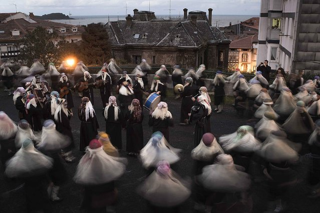Townswomen dressed as Lamia, with their faces painted white and eyes darkened, sing and dance in the Basque coastal town of Mundaka on Carnival Sunday, February 15, 2015. The Lamia are Basque mythological creatures whose lower extremities are those of a duck or fish depending on their proximity to the sea, and whose favored activity is combing their long blonde hair with a golden comb. (Photo by Vincent West/Reuters)
