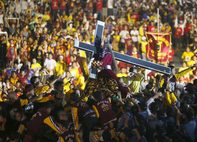 Catholic devotees mount the image of the Black Nazarene on a carriage as other devotees jostle to get closer to kiss and rub with towels its cross during a raucous procession to celebrate its feast day in Manila, Philippines, Saturday, January 9, 2016. (Photo by Bullit Marquez/AP Photo)