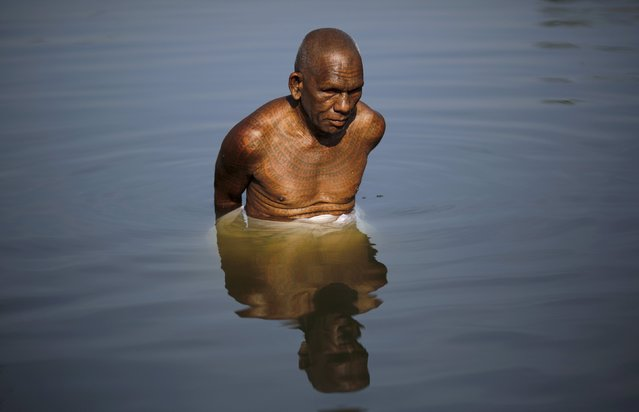 Visually-impaired Kartik Ram Sadhu, 67, a follower of Ramnami Samaj, and who has tattooed the name of the Hindu god Ram on his body, bathes in a pond in the village of Arjuni, in the eastern state of Chhattisgarh, India, November 15, 2015. (Photo by Adnan Abidi/Reuters)