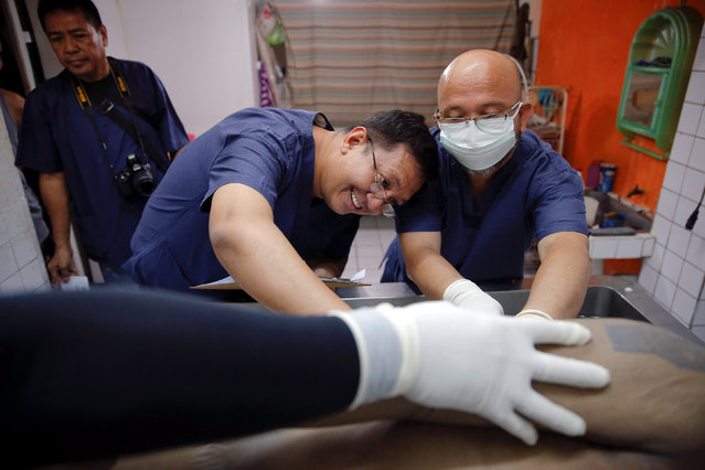 Joseph Jimenez (C), a forensic expert from the Philippines Commission on Human Rights (CHR), and his team perform an autopsy on Florjohn Cruz at Eusebio Funeral Service in Manila, Philippines October 28, 2016. (Photo by Damir Sagolj/Reuters)