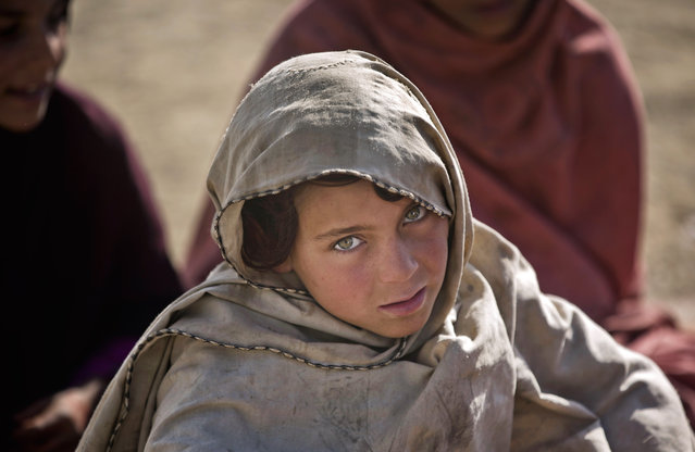 In this Monday, January 19, 2015 photo, a Pakistani refugee schoolgirl attends class at Gulan camp, some 20 kilometers (12 miles) from the border in the restive Khost province, Afghanistan. For decades Afghans have fled into Pakistan to escape war and upheaval, but in recent months the tide has reversed, with some 60,000 Pakistanis - more than half of them children – taking refuge in the Gulan camp. (Photo by Massoud Hossaini/AP Photo)