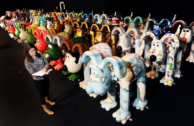 File photo dated October 10, 2013 of Dani Marlborough from Gromit Unleashed among some of the giant Gromit sculptures, decorated by celebrities and artists, as they are prepared for auction in aid of Bristol Children's Hospital charity, Wallace and Gromit's Grand Appeal. More than one million people are estimated to have visited giant Gromit sculptures exhibited around a city. (Photo by Tim Ireland/PA Wire)