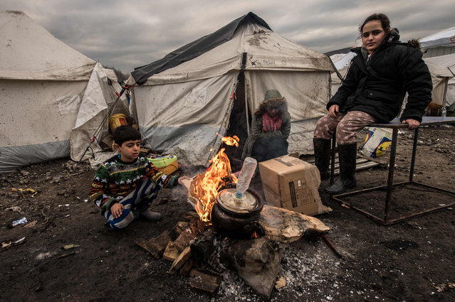 """Young migrants get warm around a brazier in the migrants camp of Grande-Synthe, near Dunkirk, on January 20, 2016, where almost some 2,500 migrants and refugees live, mostly Iraqi Kurds and Syryans. Authorities in the northern French port of Calais were struggling to move hundreds of migrants into refitted shipping containers ahead of plans to bulldoze part of the notorious """"Jungle"""" camp. There wre also attempts to relocate 2,500 migrants camped some 40 kilometres (25 miles) up the road from Calais in Grande-Synthe. (Photo by Philippe Huguen/AFP Photo)"""