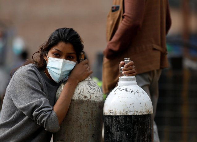 A woman holds on to the oxygen cylinders for a patient after refiling them at a factory, amidst the spread of coronavirus disease (COVID-19) surge as India's outbreak spreads across South Asia, in Kathmandu, Nepal on May 9, 2021. (Photo by Navesh Chitrakar/Reuters)